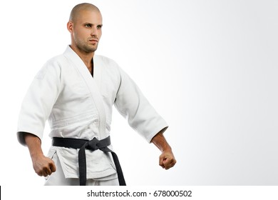 Young man fighter in white kimono with black belt for judo, jujitsu posing on isolated white background, hands holding sideways