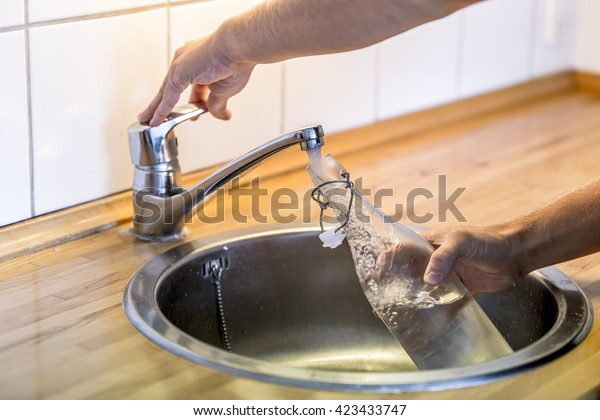 Young man filling up a carafe with water in the sink in kitchen at home.