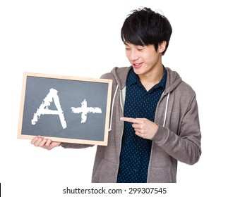 Young man finger point to chalkboard showing sign of A plus