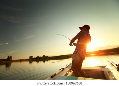 Young man fishing from a boat at sunset