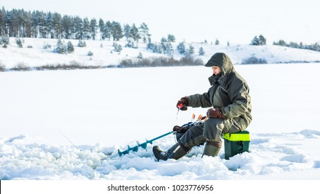 A young man is fishing from a hole on ice. Winter fishing.