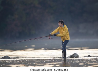 Young man fishing on Danube river in autumn time