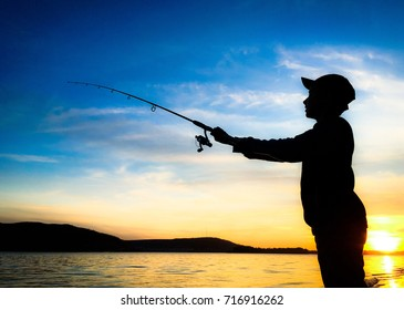Young man fishing on a river from the coast at sunset