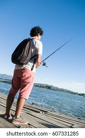 Young Man fishing in the summer at Rapel Lake, Chile