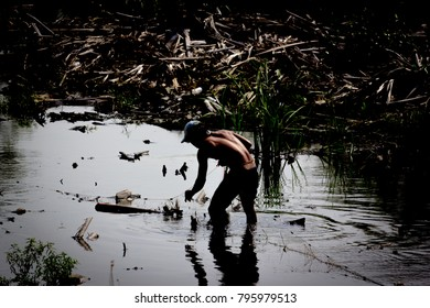 Young Man fishing in swamp. Low key light and silhouette fisherman.