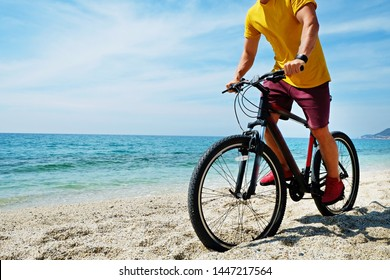 Young man with fit body riding the mtb mountain bike on sandy beach with beautiful azure water sea view. Muscle male wearing bright yellow t-shirt cycling on ocean shore. Close up, copy space.