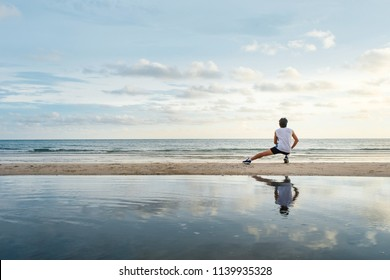 young  man with fit strong body training on beautiful Summer sunset beach sand running barefoot in sport well being and healthy lifestyle concept