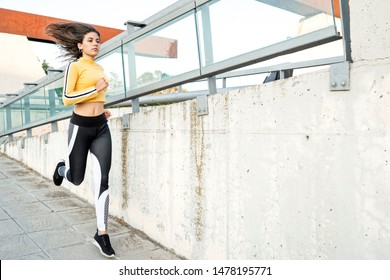 Young man with fitness lifestyle runs and his hair moves in the wind, is dressed in tight leggings, sportswear and a yellow shirt. urban sport concept in the city streets