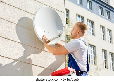 Young Man Fitting TV Satellite Dish To Wall