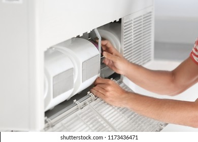 Young man fixing air conditioner at home, closeup