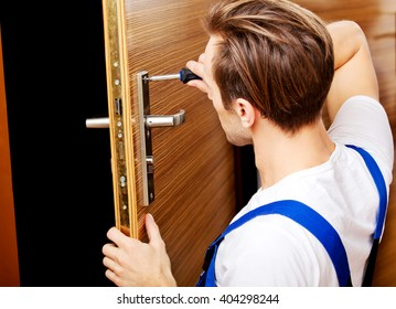 Young man fixing the door with screwdriver