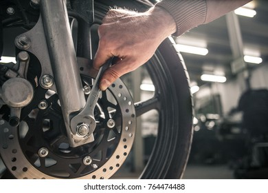 Young man fixing motorcycle. Man's hobby concept