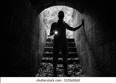 Young man with a flashlight enters the stone tunnel and looks in the dark, monochrome photo