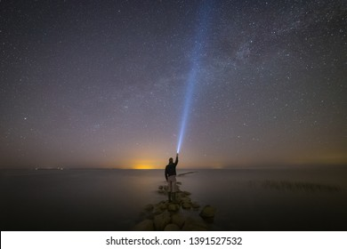 Young man with a flashlight on the edge of a stone pier late at night.
