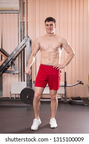 Young man flexing muscles with barbell in gym. Close-up.