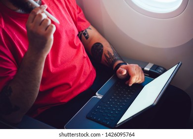 Young man flight passenger connecting to wireless internet on board with touch pad while sitting next to aircraft cabin window. Mock up blank screen for web template, thinking on work planning