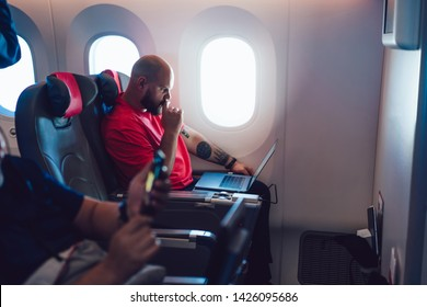 Young man flight passenger watching movie on board via entertainment Tv while sitting in comfortable airplane seat next to aircraft cabin window. Caucasian man enjoying travel via business class