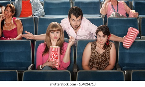 Young man flirts with girls in a theater