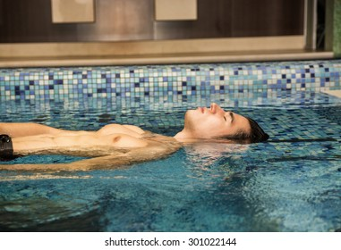 Young Man Floating Half Out of Water in Swimming Pool, Relaxing in Tranquil Setting