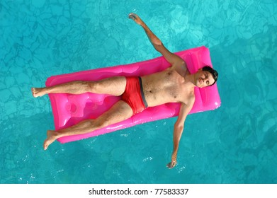 Young man floating on a mattress in water pool