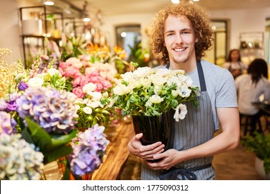 Young man as a florist between fresh cut flowers in the flower shop