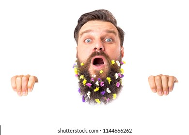 Young man with flowers in his beard with funny expression over white