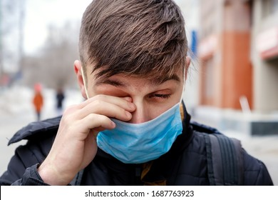 Der junge Mann in der Grippemaske in der City Street raub sein Auge