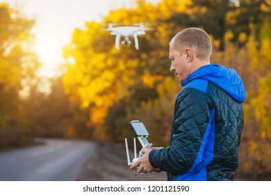 Young man with flying drone in the autumn park. Man with remote controller in his hands taking aerial photos and videos