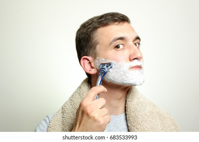 Young man with foamshaving his cheek by razor