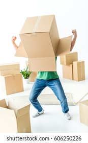 Young man fooling around with cardboard box on his head isolated on white