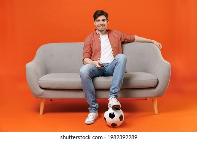 Young man football fan in shirt support favorite team with soccer ball sit on sofa at home watch tv live stream switch channel isolated on orange background. People sport leisure lifestyle concept.