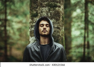 Young man in a forest leaning on a tree with eyes closed, individuality and nature concept