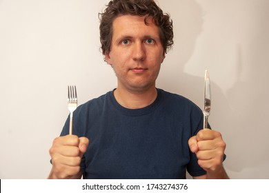 Young man with fork and knife. Concept of ready to eat, hungry, delicious.