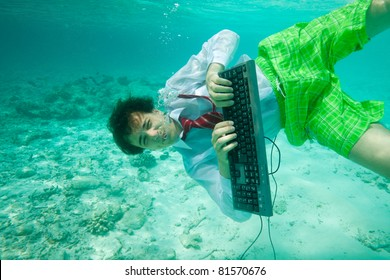 Young man in formal clothes with keyboard working and swimming underwater