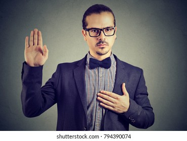 Young man in formal clothing and eyeglasses swearing in being trustworthy while looking at camera.