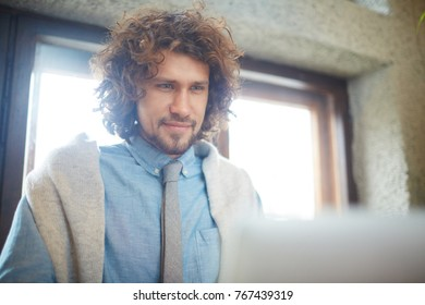 Young man in formalwear looking at laptop display during work