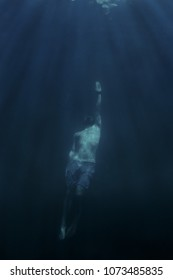 Young man free diver swimming up to the surface.
