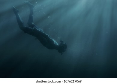 Young man freediver swimming with mask and snorkel underwater in deep sea among sunbeams.