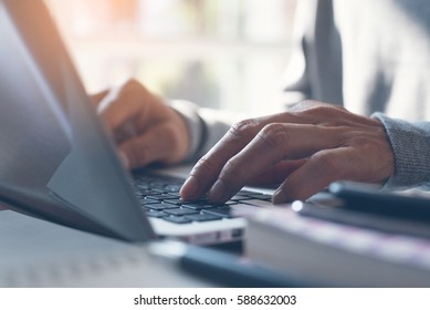 Young man or freelancer using laptop computer, searching web with morning light, browsing internet information, working from home concept, close up