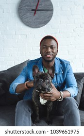 Young man with French bulldog sitting on sofa