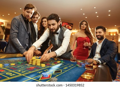 A young man with friends makes bets on roulette in a casino.