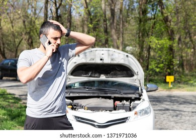 Young man in front of broken down car on the road, calling for HELP