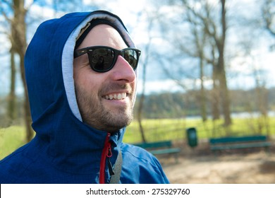 young man in front of nature background with hoodie sweater is smiling