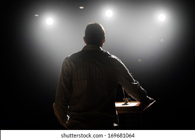 a young man in front of a podium and an audience