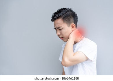 Young man is frowning painfully with hand over his neck