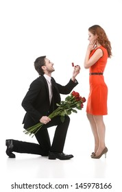Young man in full suit standing on one knee and making a proposal to his girlfriend against white background