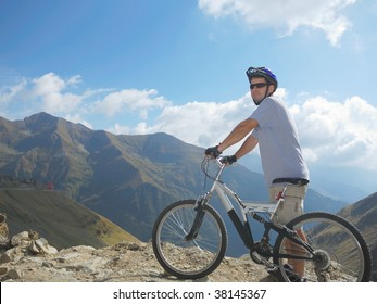 young man with a full suspension bike in mountains environment