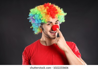Young man in funny disguise on grey background. April fool's day celebration