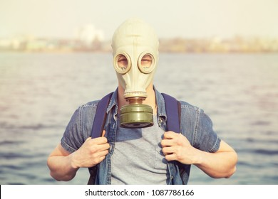 A young man in a gas mask on a summer day. Air pollution by carbon monoxide emissions. Breathe through the gas mask filter.