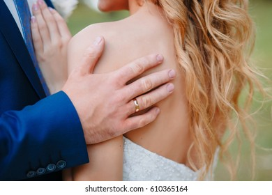 A young man gently embraces his bride in a wedding dress by the shoulders to the goosebumps. Young girl with clavicles and an open neckline. Wife and husband. Groom kisses bride's neck